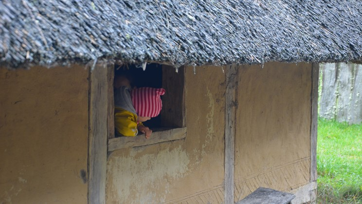 Little Girl Peeking out of an Iron Age House